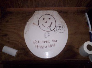 "A white toilet seat with a smiley face and a speech bubble saying ""Feed me!"", with the words ""Welcome to Happy Hill"" beneath it"