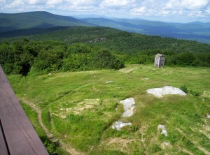 The view north on the A.T. from the observation tower on Bromley Mountain; a large rectangular concrete block with white blazes painted on it is in view