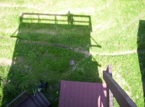 The observation tower and me in shadows, as seen from the top of the tower, with my backpack lying at its base