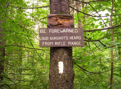 A white blaze on the trail north of Greylock, with a sign noting a nearby rifle range
