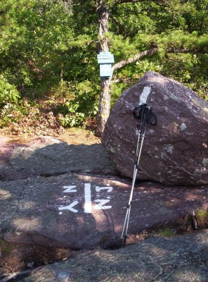 The New York - New Jersey state line, marked by white painted abbreviations and a line on a large rock, with a blaze and trail register off the side of the trail