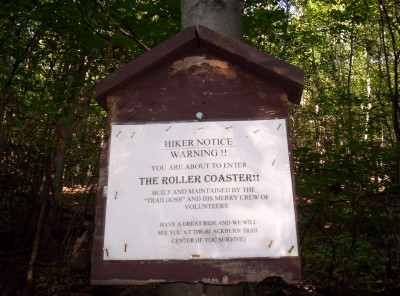 "A sign with these words on it: Hiker Notice Warning!  You are about to enter the Roller Coaster!!  Built and maintained by ""Trailboss"" and his merry crew of volunteers.  Have a great ride and we will see you at the Blackburn Trail Center (if you survive)"