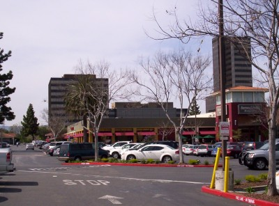 A shot with a building in the background and parked cars in foreground