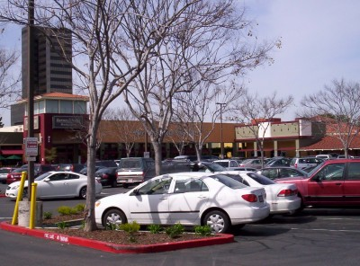 Panned right, cars in the foreground with low building spanning width of picture in distance