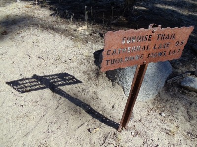 A Yosemite backcountry trail sign, marking Sunrise Trail, made of rusted metal with lettering cut through it, followed by a long midafternoon shadow, in which the gaps of the sign's letters are visible