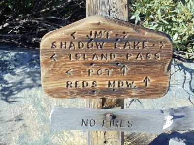 Trail sign at Thousand Island Lake for the PCT/JMT split: the PCT heads straight toward the ridge, while the JMT continues to the right around half a dozen lakes