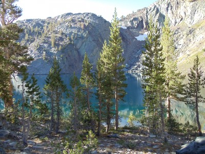 Teal-blue Ruby Lake, ringed by cliffs and a gently sloping trail through trees