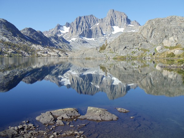Mount Ritter and Banner Peak, mirrored in Garnet Lake; the mirror effect progresses from near-perfect closest to the camera to significantly blurred in the distance, as slight ripples in the water accumulate to distort the reflection