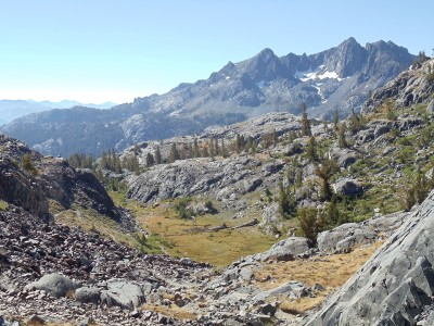 The start of the descent past Shadow Lake toward Devils Postpile; far in the distance lies the black Volcanic Ridge