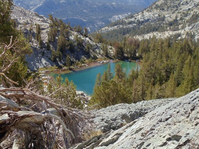 The teal lake is surrounded by rocky slopes sprinkled with evergreens