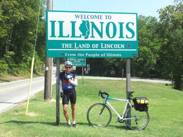 "Me standing underneath a ""Welcome to Illinois"" sign, with my bike leaning against the sign just next to me; a sign with directions to a mental health center is just visible"