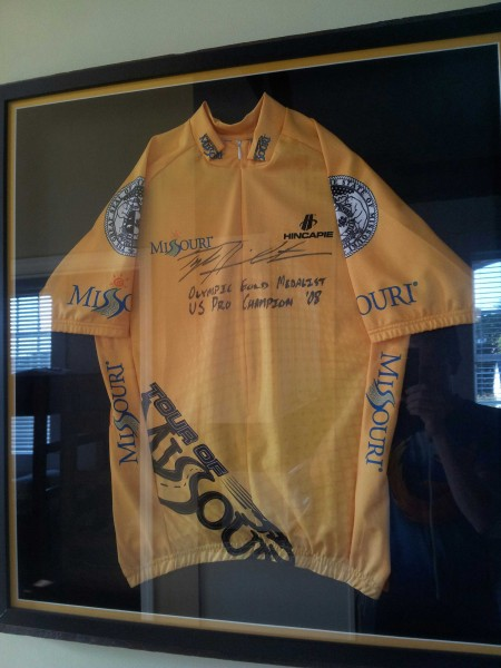 "A signed Tyler Hamilton Tour of Missouri jersey; written across it are ""Olympic Gold Medalist"" and ""US Pro Champion '08"""