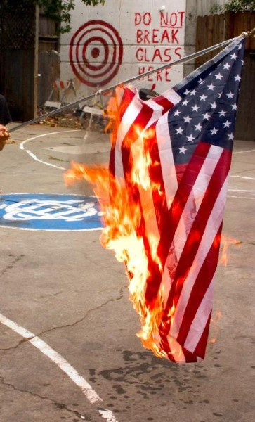 An American flag held, burning, touching the ground