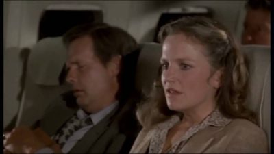 Woman with an anxious look on her face, sitting in a seat on an airplane -- from that great classic, Airplane!